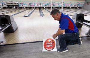 Don Klackner Applying Sticker for Safe Distancing